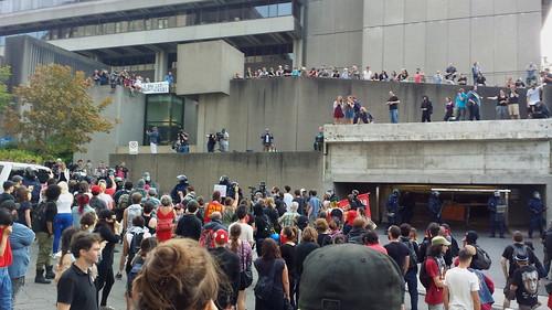 Environ 200 personnes au sol, mais aussi sur les galeries de béton du bâtiment complexe.  La porte du stationnement est ouverte et une ligne antiémeute s'est formée devant. Les gens discutent calmement.