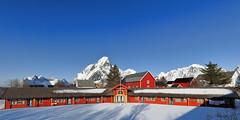 Long red cottage-rorbu in Reine village. Olstinden-Klokktinden-Lilandstinden-Festhaeltinden mounts background. Lofoten-Nordland-Norway.0304