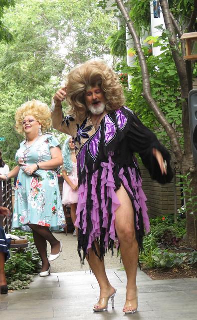 Photo of Scott Sanders in a dress in heels followed by a drag queen.