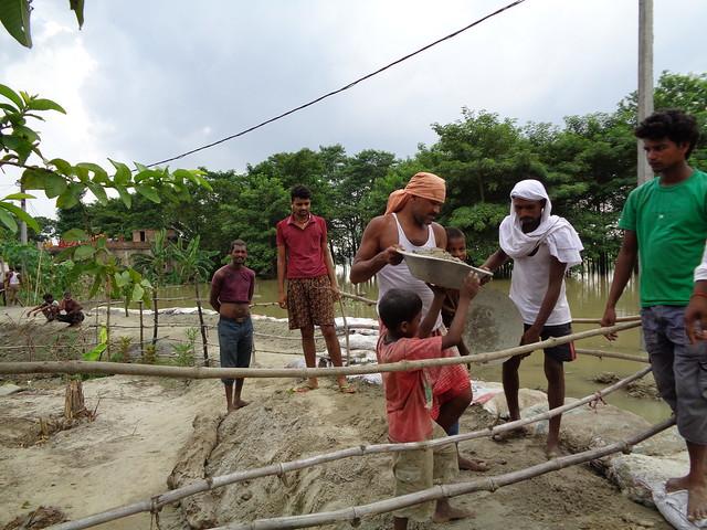 विजय छपरा के वार्ड 8 में बांध पर मिट्टी डालते लोग