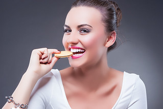 Food Concepts. Portrait of Young Smiling Happy Brunette Girl Eating Round Cookie. Demonstrating Enjoyment and Pleasure.Against Gray
