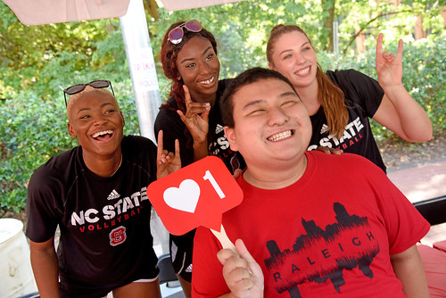 Wolfpack volleyball fan is all smiles while posing with a few members of the team.
