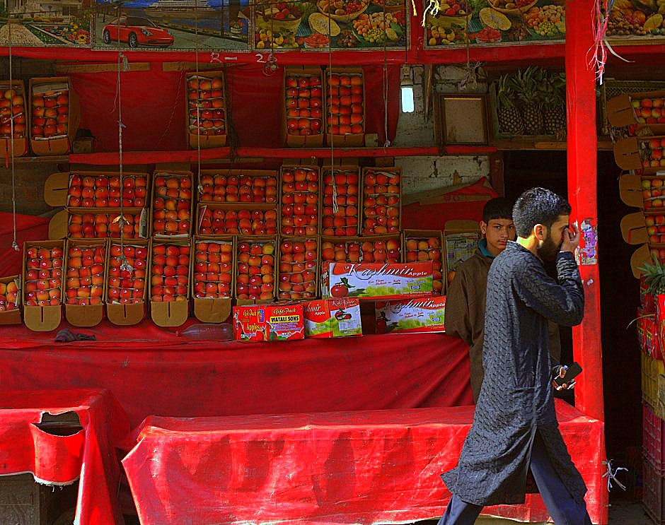 Kashmiri man walking in front of fruit shop in Srinagar