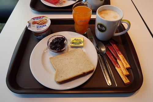 Milchkaffee, Multivitaminsaft, Walnussjoghurt und Toast mit Butter und Brombeermarmelade