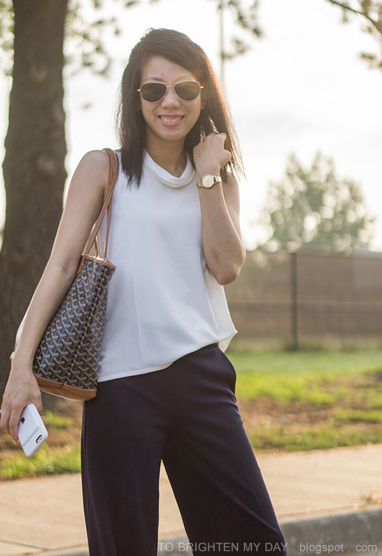 white mock neck sleeveless top, navy wide legged pants, gold watch, monogrammed tote