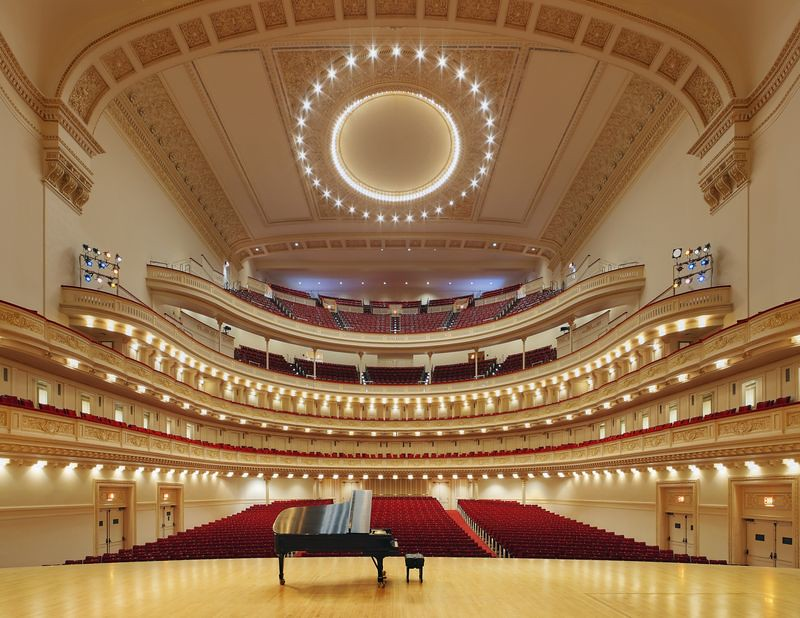 Photo of piano on stage in large empty concert hall