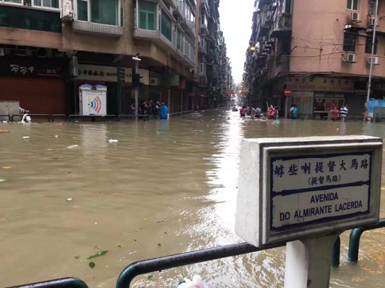 澳門罅些喇提督大馬路一帶受大雨影響,水深及腰,不少市民需要澗水而行。(澳門特約記者攝)