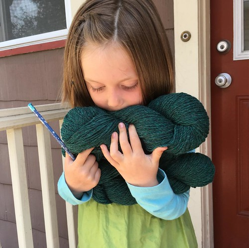 """Huffing wool fumes, just like mama. (The yarn for her green """"Peg+Cat"""" cardigan arrived. It's from Beaverslide, because I'm very predictable!)"""