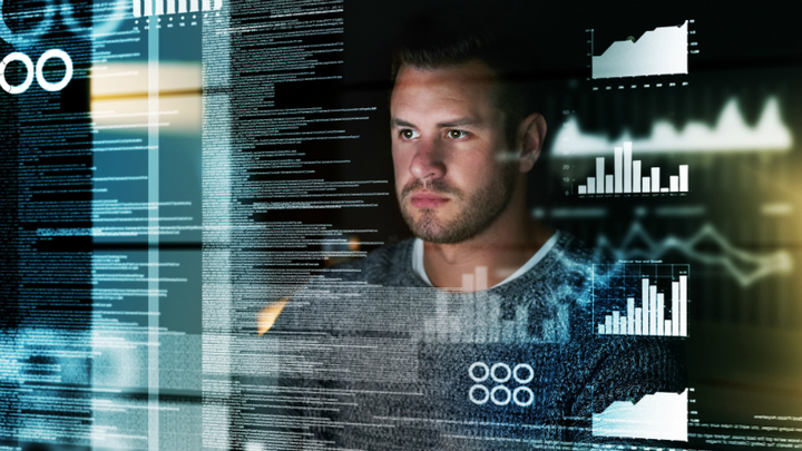 A man gazes at data on his computer screen