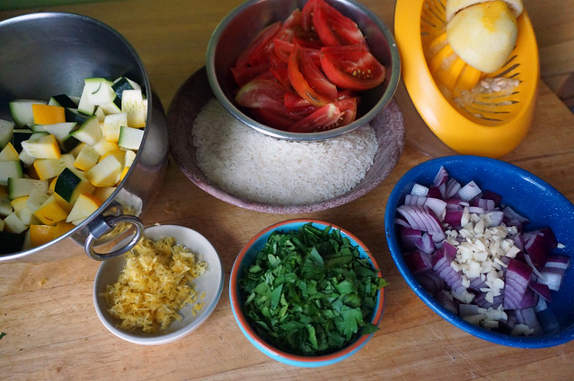 The same ingredients from the earlier still life shot, but now prepped: cubed squashes, tomatoes in wedges, onion diced and sprinkled with garlic, lemon divided into a pile of fluffy zest and a spent rind on a juicer.