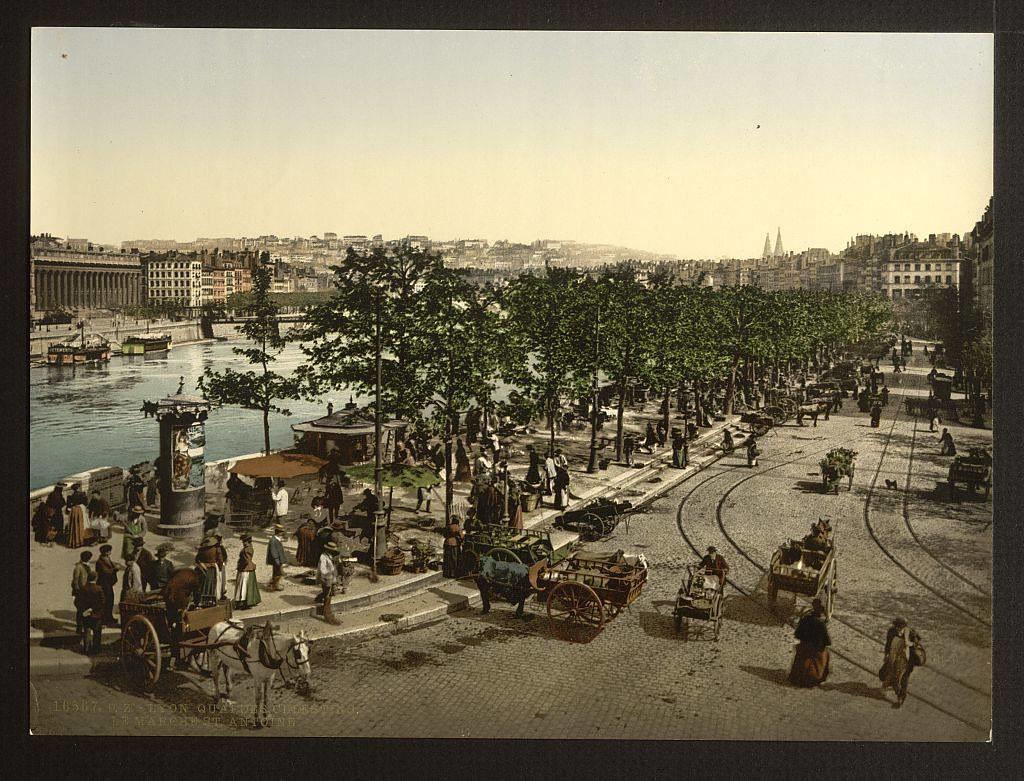 Quai de Saône à Lyon pendant une journée de marché. Les camionnettes ont remplacé les chevaux et leurs carioles. Des bateaux sont amarrées le long des berges. Les arbres remontent tout en haut du quai jusqu'au pont reliant St Jean (au premier plan).