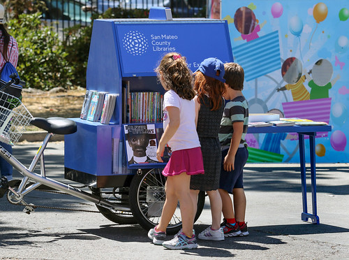Children looking at books on the Book Bike.