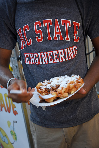 An engineering student enjoys some fried dough at Packapalooza.