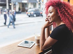 Beautiful girl in a cafe talking on smart phone