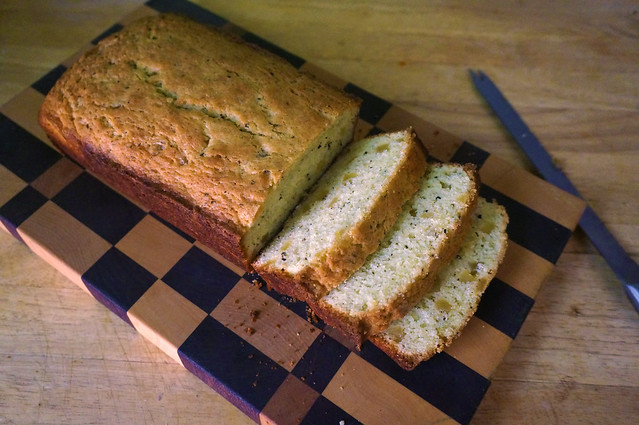 The classic sliced-loaf shot: a loaf of cake on a decorative wooden cutting board, three slices falling open like a fan exposing the crumb studded with small yellow squares of ginger and little black flecks of pepper.