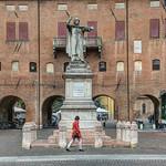 Woman walking by the monument to Girolamo Savonarola in Savonarola square in Ferrara
