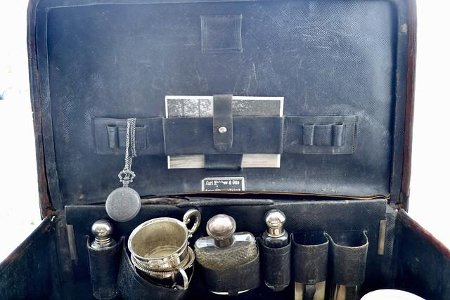 Zwarte oude koffer met flesjes