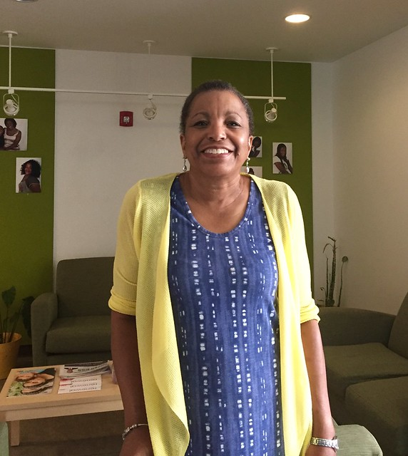 Photo of Wanda Steptoe smiling while she stands inside a green and white living room area at one of New Endeavors by Women's