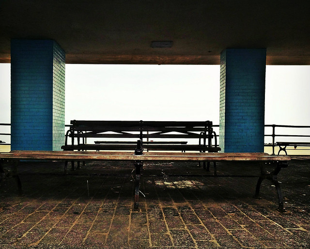 Old Grey Bench Between Walls of Blue