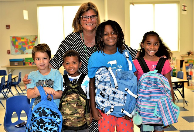 Lori Bailey, site director of Wilmington University's Dover campus and board member with the Greater Dover Boys and Girls Club, poses with beneficiaries of WilmU's backpack campaign. (Photo courtesy of James Jones.)