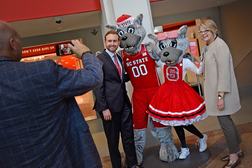 """Board of Governors' Tyler Hardin and UNC system president Margaret Spellings (right) pose for a quick photo with Mr and Ms Wuf """"statues"""" in Reynolds Coliseum."""