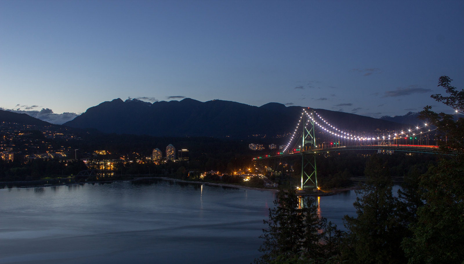 View over the Lion's Gate Bridge to North Vancouver and mountains at night