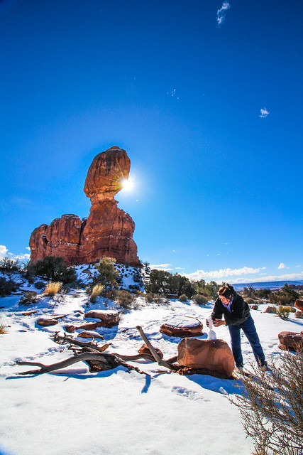 Mom playing in the snow under Balance Rock in Arches National Park, Utah