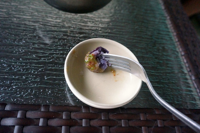 A small purple potato, broken in half and speared on a fork, with orange-green sauce coating one end of the bite.