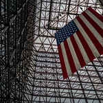 A giant U.S. flag hangs from the atrium of the John F. Kennedy Presidential Library and Museum.