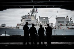 Sailors observe a refueling-at-sea USS Sampson from the hangar bay of USS Theodore Roosevelt.