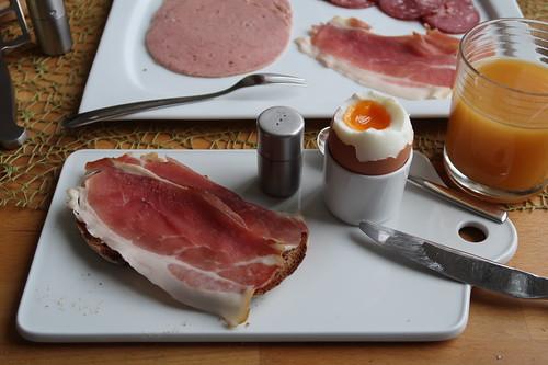 Roher Schinken auf Holzofenbrot zum Frühstücksei