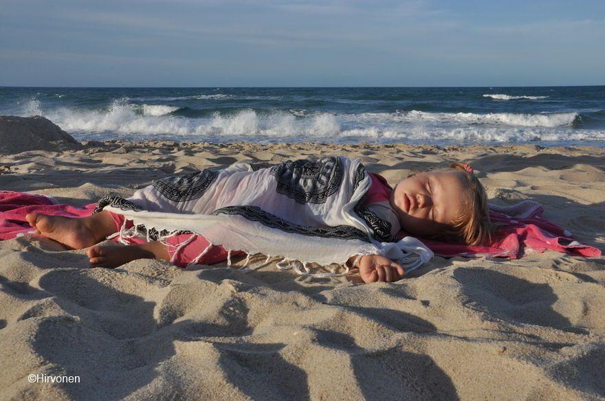 Lasten kanssa matkustaminen | Pikkutyttö nukkuu rannalla.