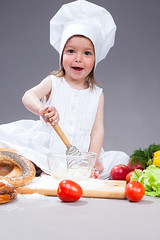 Funny Smiling Caucasian Girl In Cook Uniform Making a Mix of Flour, Eggs and Vegetables With Whisk In Studio Environment.