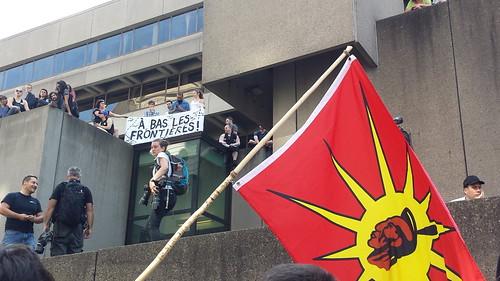 Plus haut sur le bâtiment, il y a une bannière « À bas les frontières ».  Le drapeau rouge des Premières Nations est aussi très visible dans la photo : voir l'explication sous les photos. Des gens sympathisants à la manif antiraciste se tiennent sur les plateaux élevés comme des galeries. Il y a aussi au haut plusieurs photographes des médias.