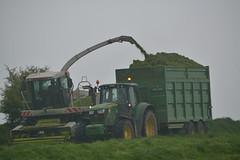Claas Jaguar 890 SPFH filling a Broughan Engineering Mega HiSpeed Trailer drawn by a John Deere 6150M Tractor