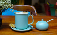 A blue cup of coffee on wooden table at coffee shop