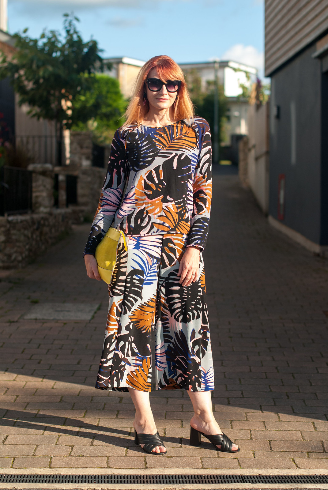 Late summer outfits - Palm print co-ords: Long sleeve top and wide leg crop trousers culottes pants \ yellow suede clutch bag \ black crossover block heel mule sandals \ statement oversized earrings \ cat eye sunglasses | Not Dressed As Lamb, over 40 style