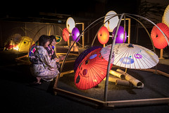 Mother and daughter in yukata sitting in cadle lights in paper u