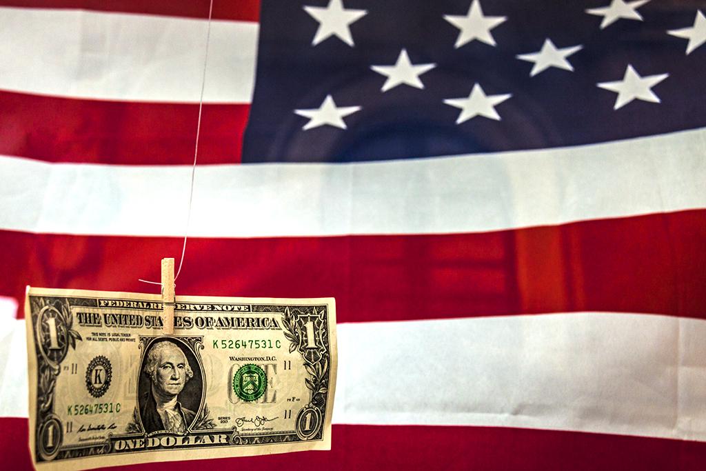 Dollar dangling in front of American flag--Tarragona