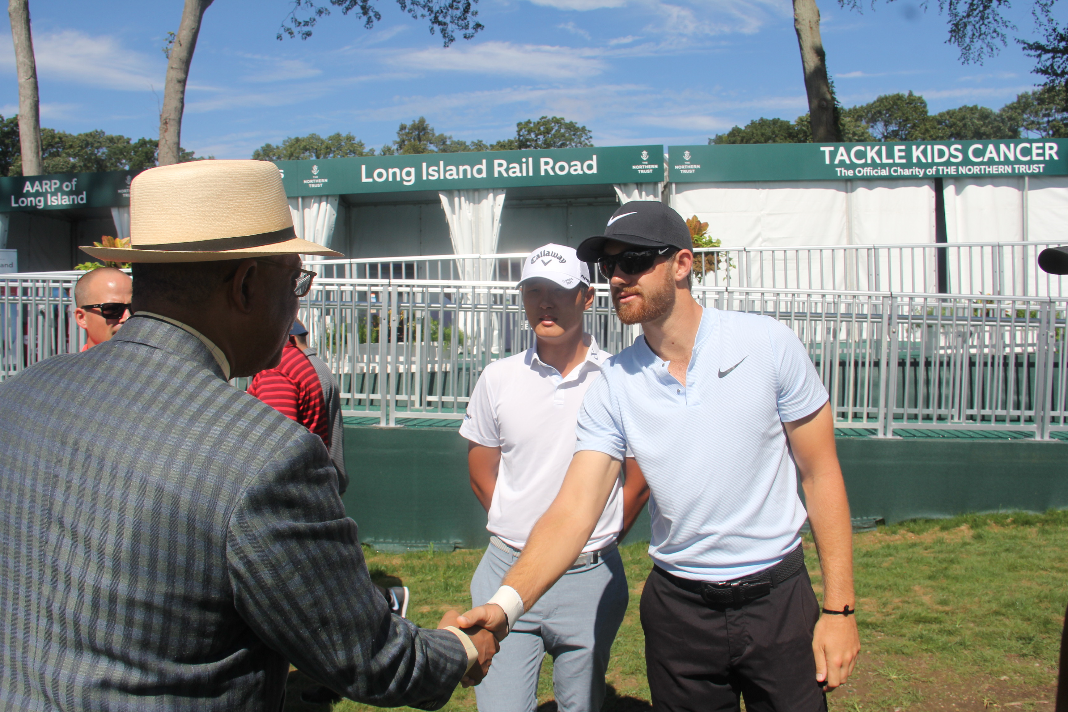 President Butts shakes hands with two PGA players