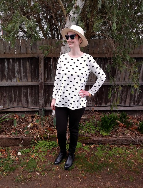 An image of a woman standing in front of a fence with trees. She wears a long sleeve knit tee in black and white with cat head print, black slim pants, black boots and a hat and sunglasses. Her hand is on her hip and she is smiling.