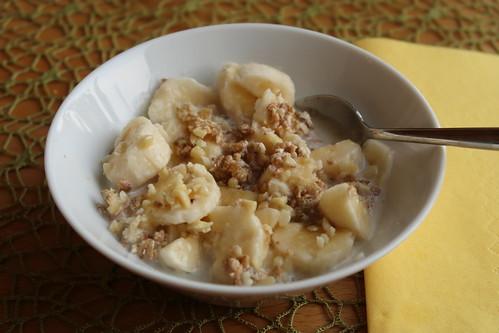 Frisch geflockte Körner mit heißer Milch, Banane, Honig und Mandelsplittern