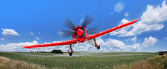 An athletic light-engine aircraft flies over the field. Aviation in agriculture. Adrenaline, the concept of travel.