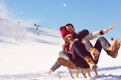 Young Couple Sledding And Enjoying On Sunny Winter Day Using Venture Heat On Demand battery powered and USB powered Heated Clothing, Heated Jackets, Heated Vests, Heated Hoodie, Heated Sweaters, heated gloves, heated mittens, heated pants, heated shirts