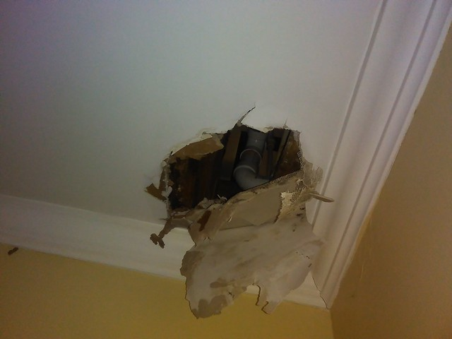 Photo showing a large hole in the ceiling, with plaster hanging down and pipes exposed behind it.