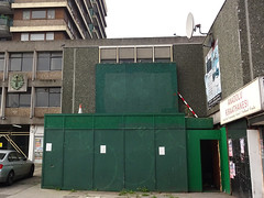 A grey, blocky building on several levels.  The part in the centre of the photo has been boarded up with dark green hoardings.  A stylised zodiac plaque is on the frontage in the background.