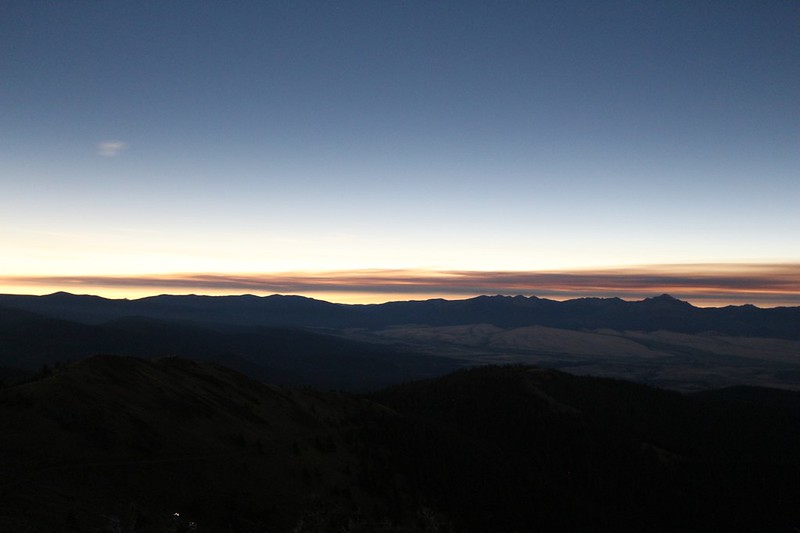 View to the west of light in the distance but dark mountains and clouds nearby during the total solar eclipse