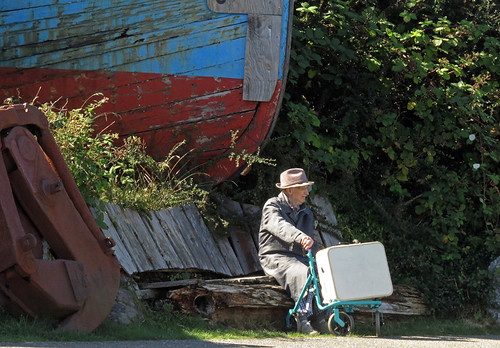 Boat and an old man with a suitcase waiting for a bus in Ucluelet
