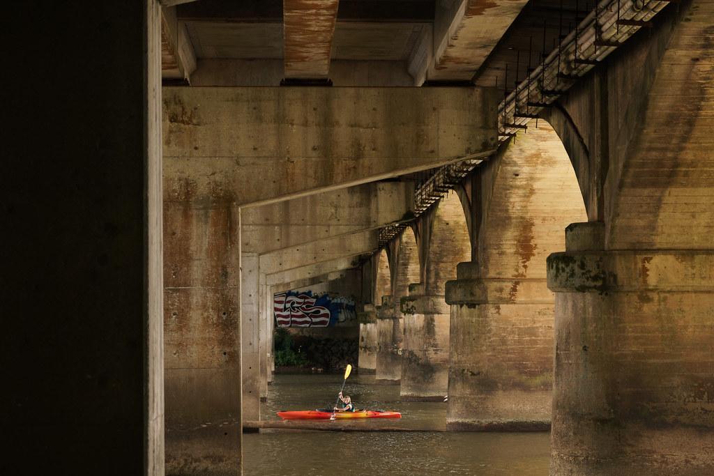 A kayaker paddles under a bridge over the Chattahoochee River in Atlanta, Georgia