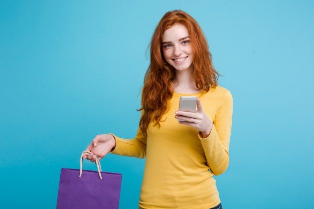 shopping-concept-close-up-portrait-young-beautiful-attractive-redhair-girl-smiling-looking-at-camera-with-shopping-bag-blue-pastel-background-copy-space_1258-840